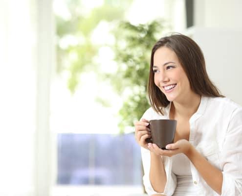 Afslappet sensitiv kvinde drikker kaffe eller the og har sensitiv venlig livsstil