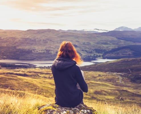 Nyhedssøgende kvinde kigger ud over langskab og laver i balance med sin sensitivitet