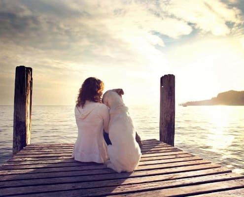 Sensitiv kvinde ved havet med hund i indre ro