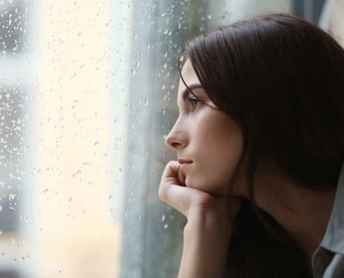 kvinde kigger søgende og spørgende ud af vindue