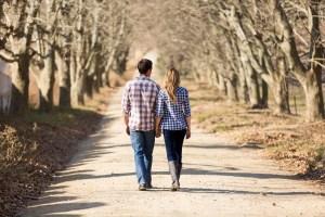 mand og kvinde i kærlighedsforhold går hånd i hånd på sti