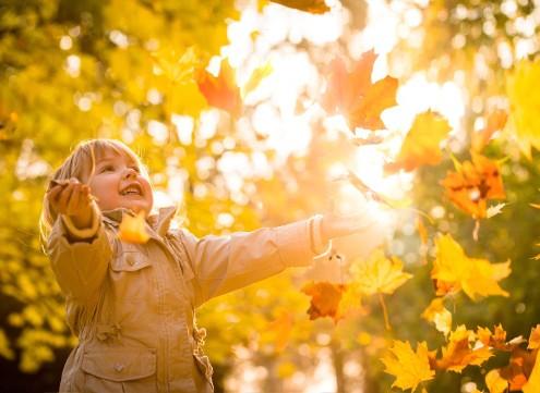 Glad pige leger med blade i efteråret og har overskud