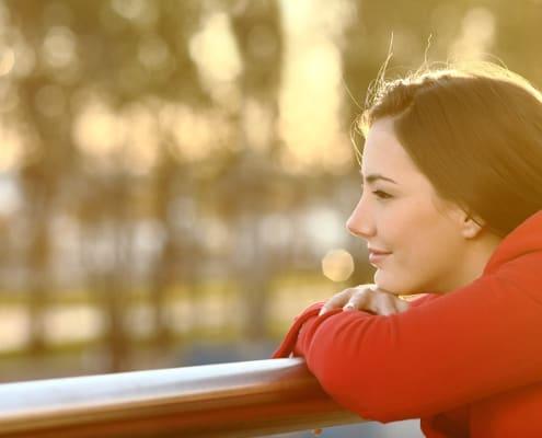 Eftertænksom kvinde kigger ud og tænker afslappet