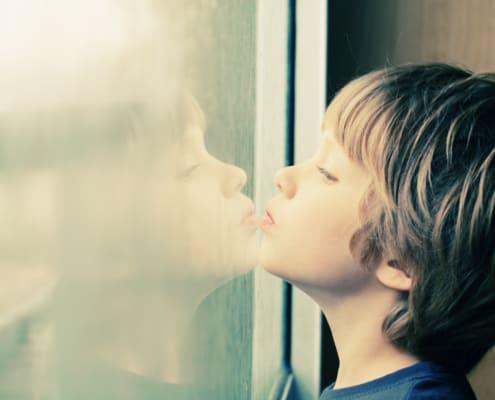 Tænksom sensitiv dreng ved vindue med traume, stress og modgang