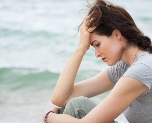 Nedtrykt sensitiv kvinde ved vandet med tegn på traume