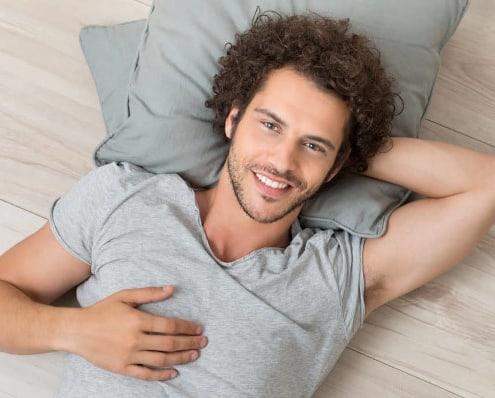 Glad sensitiv mand ligger på gulvet og har hjertekohærens