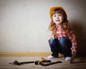 Lille glad pige klædt ud som cowboy med redskaber til at slippe bekymringer